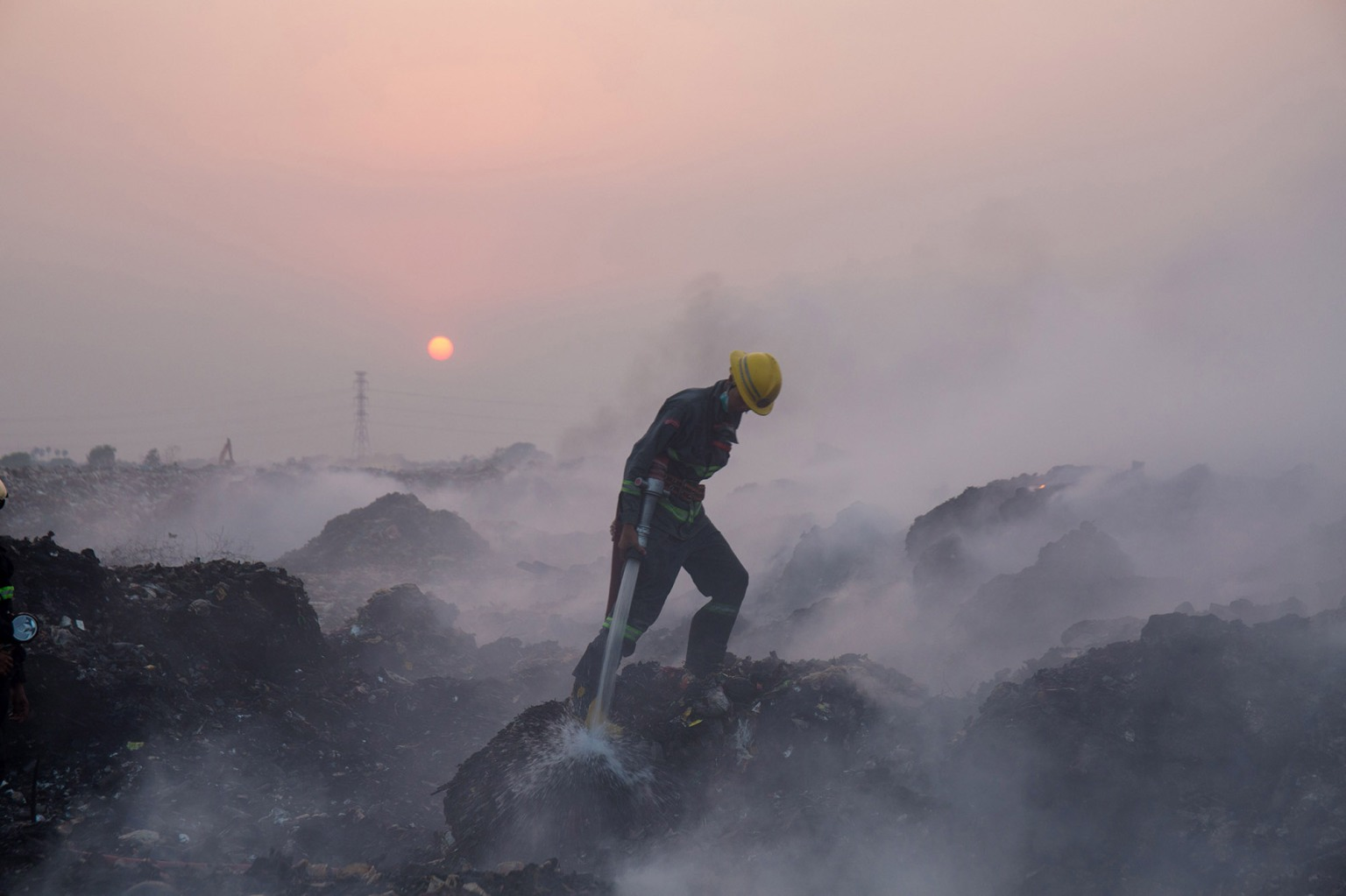 A fireman battles a fire at a massive garbage dump in Yangon, Myanmar, on April 23. The fire raged for hours, blanketing a large part of the city with foul-smelling smoke. SAI AUNG MAIN/AFP/Getty Images