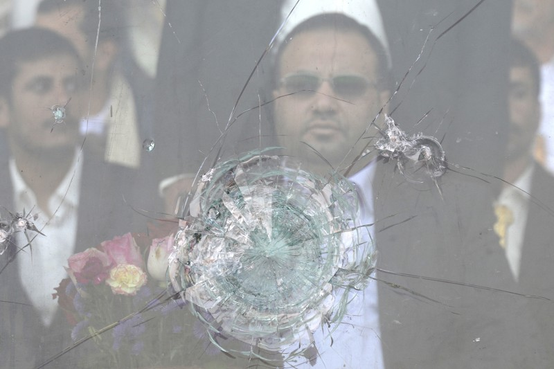 Saleh al-Samad, the president of the Houthis' Supreme Political Council, sits behind bulletproof glass at a rally in Sanaa, Yemen, on Aug. 20, 2016. (Mohammed Hamoud/Getty Images)