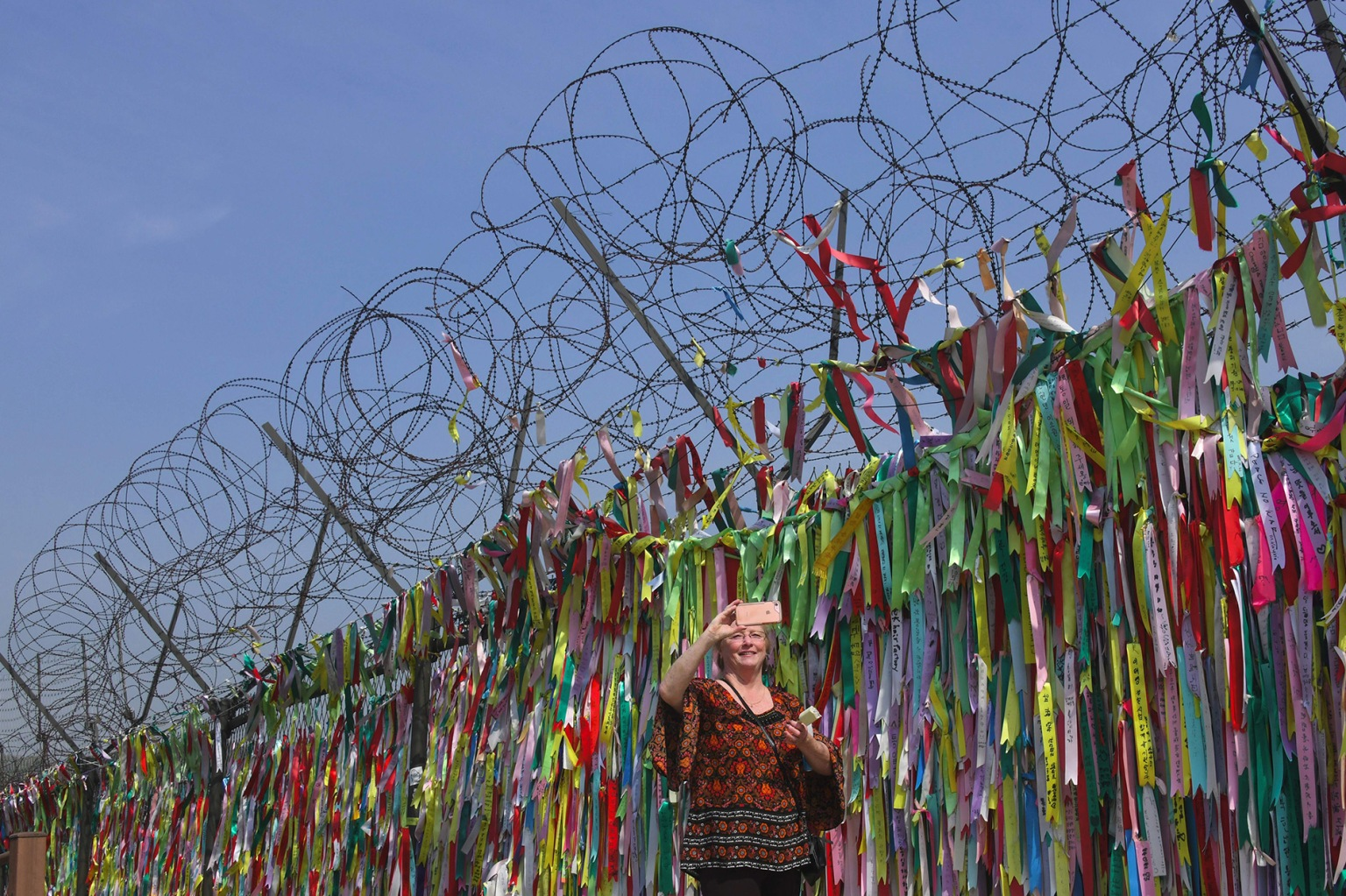 A woman poses in front of a military fence covered with ribbons calling for peace and reunification at Imjingak peace park in Paju, South Korea, near the demilitarized zone dividing the two Koreas on April 26. North Korea's leader Kim Jong Un and the South's president Moon Jae-in met at the Military Demarcation Line that divides the peninsula ahead of the inter-Korea summit in an occasion laden with symbolism. JUNG YEON-JE/AFP/Getty Images