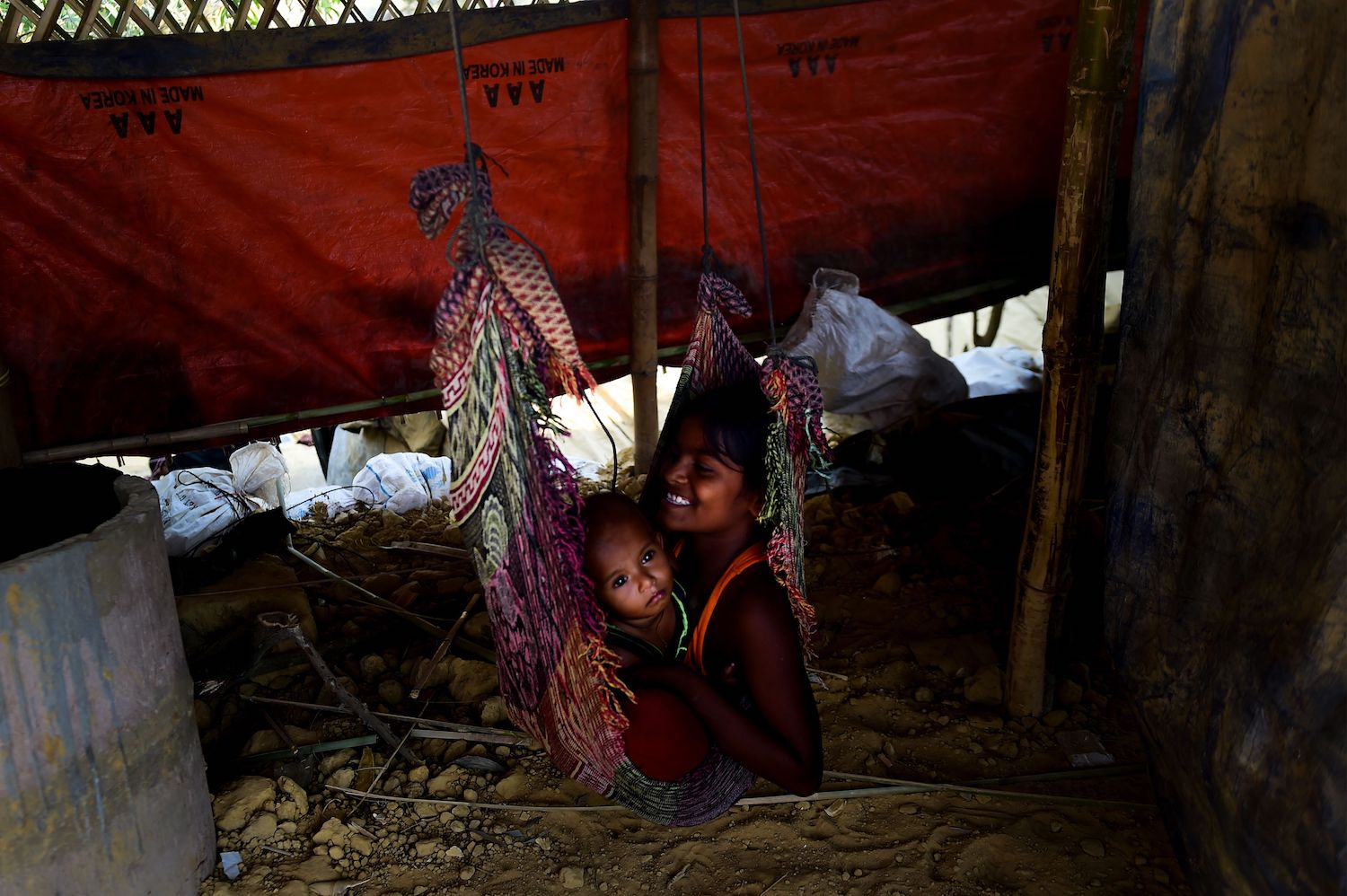 Rohingya refugee children play on a swing at Kutupalong refugee camp in Bangladesh's Ukhia district on April 9, 2018. / AFP PHOTO / MUNIR UZ ZAMAN        (Photo credit should read MUNIR UZ ZAMAN/AFP/Getty Images)