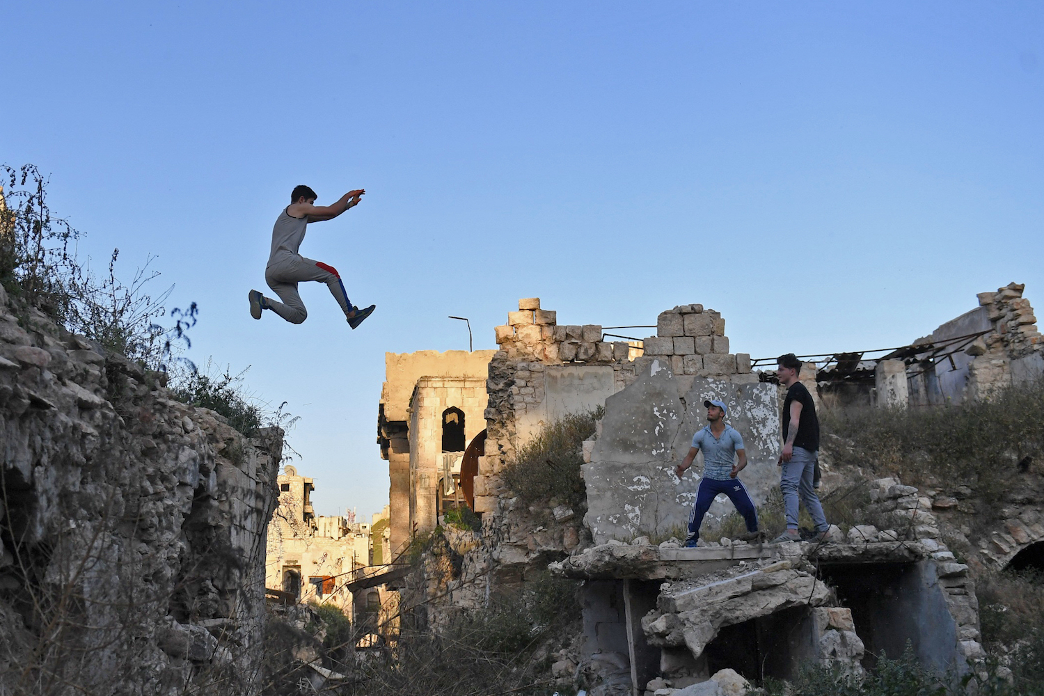 Syrian youths practice parkour in Aleppo, northern Syria, on April 7, 2018. In the absence of special facilities and equipment for the sport, such as padding to protect against falls, athletes often risk serious injury. And parkour in east Aleppo comes with an additional challenge: remnants of war.  / AFP PHOTO / George OURFALIAN        (Photo credit should read GEORGE OURFALIAN/AFP/Getty Images)