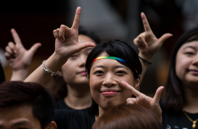 Runners of the Shanghai Pride Run make signs with their fingers while wearing rainbow shoelaces at the start of the race in Shanghai on June 18, 2016. (Johannes Eisele/AFP/Getty Images)
