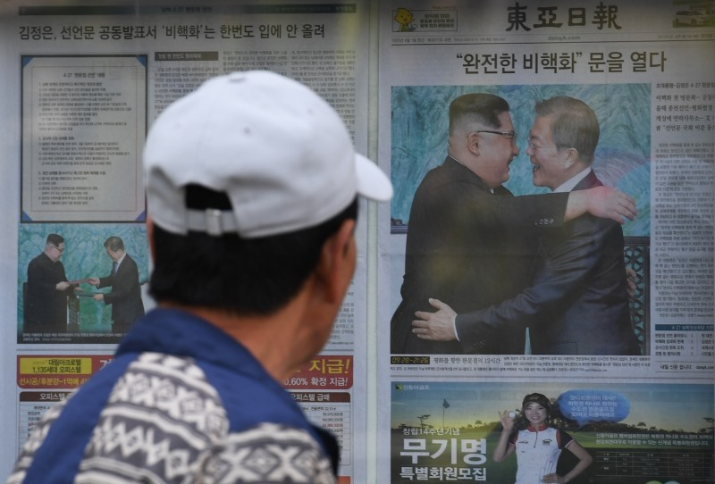 A man walks past a newspaper featuring a front page story about the summit between South Korean President Moon Jae-in and North Korean leader Kim Jong Un, on a sidewalk in Seoul on Apr. 28. (Greg Baker/AFP/Getty Images)