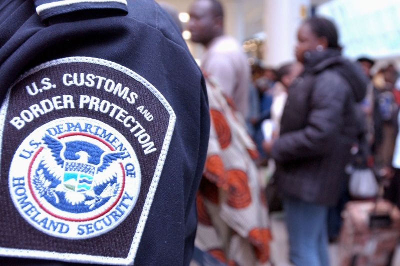 A U.S. Customs and Border Protection agent stands watch as a crowd of overseas visitors to the U.S. wait in line to pass through Customs January 5, 2004 at JFK airport in New York City. (Stephen Chernin/Getty Images)
