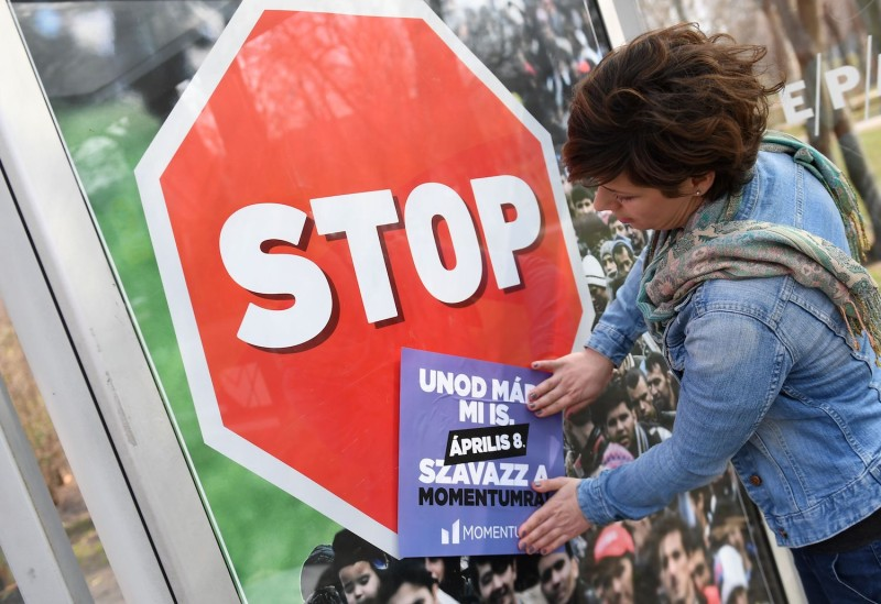 An activist of the new centrist-liberal Momentum party over-pastes an anti-migration billboard on March 28 in Budapest, Hungary. (Attila Kisbenedek/AFP/Getty Images)