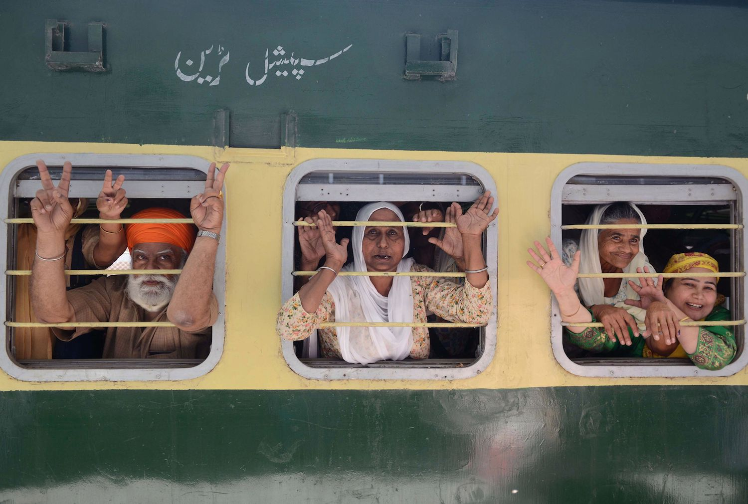Indian Sikh pilgrims wave from their train at Attari Railway Station before leaving on special service to Lahore to celebrate the Baisakhi festival in Pakistan, on the outskirts of Amritsar on April 12, 2018.