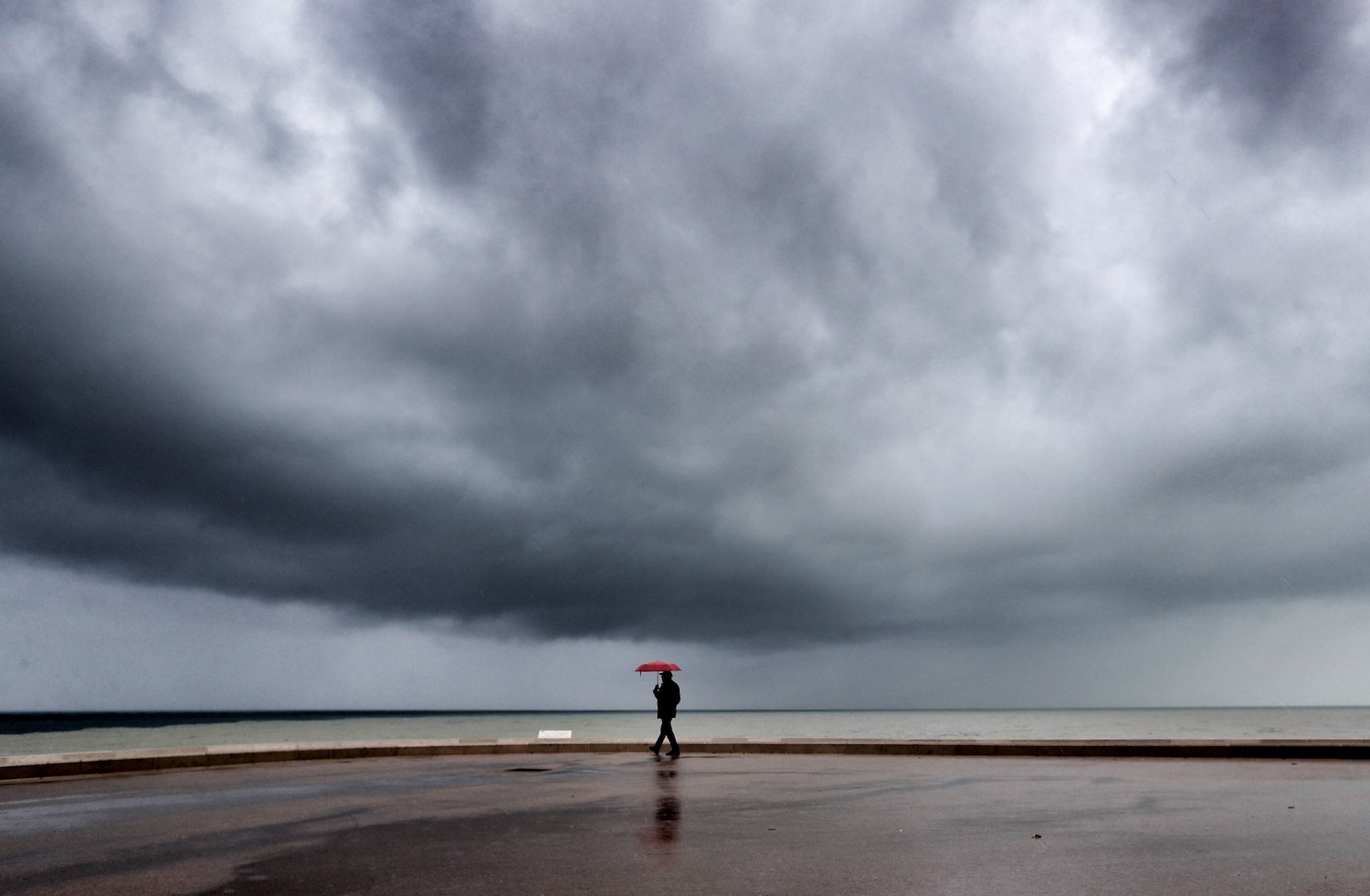 A man walks as a storm is approaching, on April 12, 2018 on the French riviera city of Nice.   / AFP PHOTO / VALERY HACHE        (Photo credit should read VALERY HACHE/AFP/Getty Images)