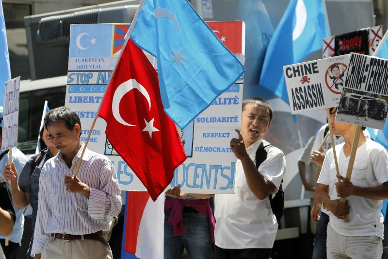 People hold placards and flags during a demonstration of France's exiled Uyghur community on July 4, 2010 in Paris.