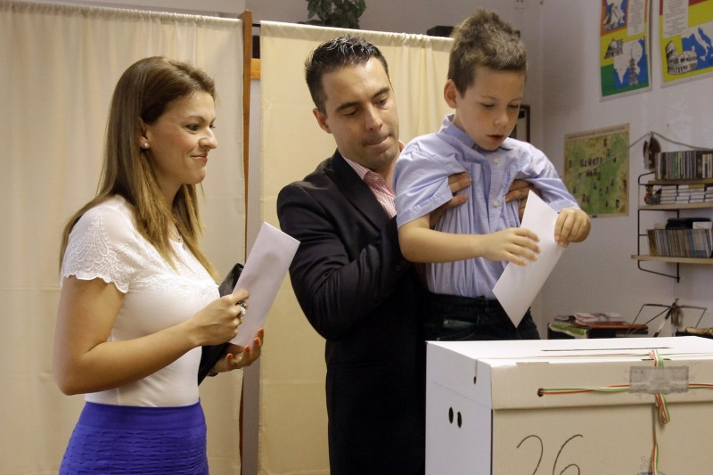 Gabor Vona (center), leader of the Hungarian far-right Jobbik party with his wife and son  casting his ballot for the European Parliment elections on May 25, 2014 at a local polling station in Budapest.
