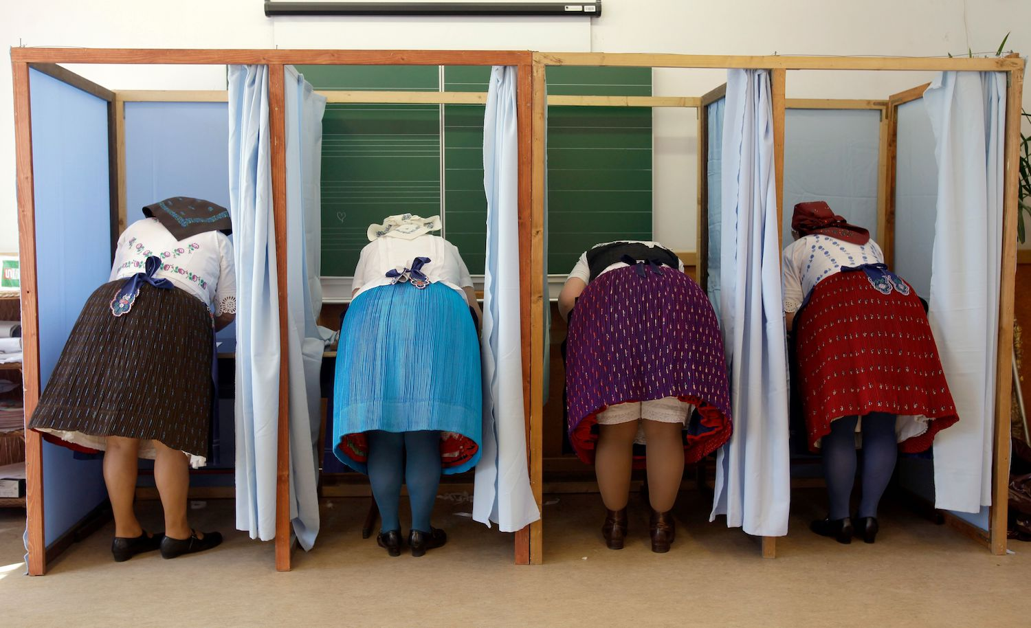 Women dressed in traditional Hungarian outfits prepare their votes in a polling station in a school in Veresegyhaz, some 30kms east of Budapest, on Apr. 8, during the general election.  Hungary votes in parliamentary elections on April 8, 2018 that will decide whether nationalist Prime Minister Viktor Orban wins an expected third consecutive term. / AFP PHOTO / PETER KOHALMI        (Photo credit should read PETER KOHALMI/AFP/Getty Images)