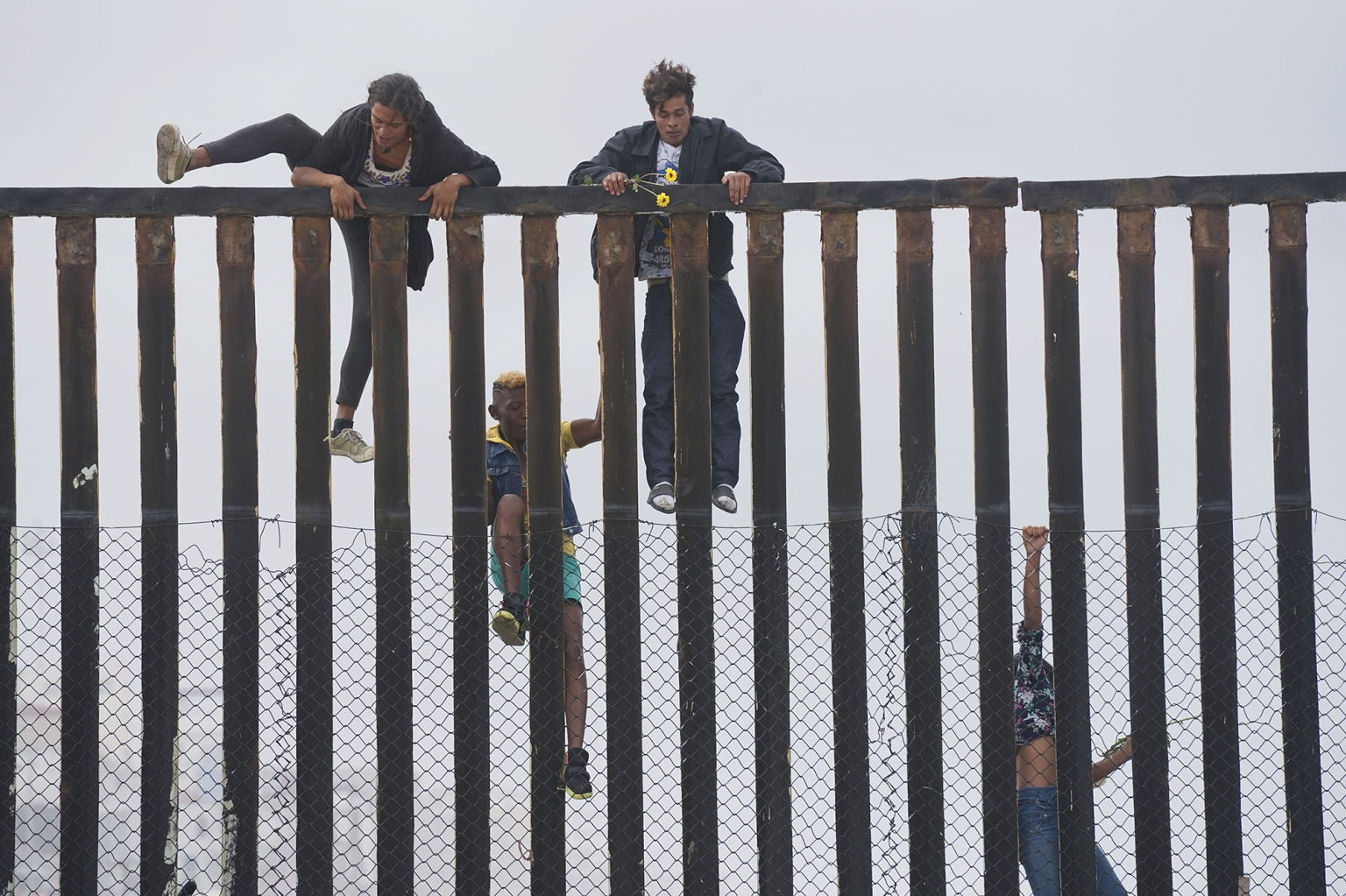 Migrant demonstrators climb the U.S.-Mexico border fence during a rally April 29 in San Ysidro, California. The U.S. has threatened to arrest migrants from the caravan that has reached the border if they try to sneak in. Organizers said May 3 that 150 from the group had crossed the border already to seek asylum. SANDY HUFFAKER/AFP/Getty Images