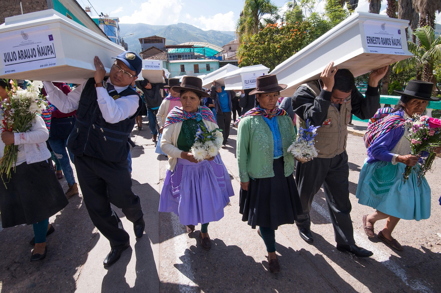 Relatives parade the coffins of their loved ones around the main plaza in Ayacucho, Peru, following a Mass on May 9. Residents received the remains of 23 relatives missing since the mid-1980s, which were recovered from mass graves and identified with DNA. Peru recently raised the official count of missing persons from its violent civil war to 20,329, a third more than previously recognized. CRIS BOURONCLE/AFP/Getty Images