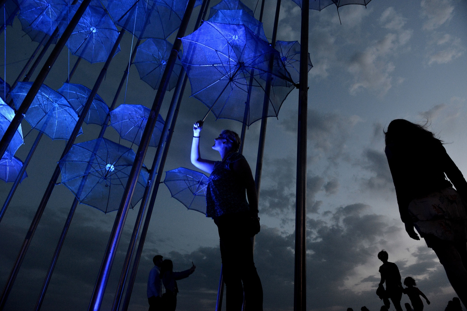 "People stand under the ""Umbrellas"" artwork by Greek sculptor George Zongolopoulos during the celebration of World Wish Day by the Make-a-Wish International charity organization in Thessaloniki on April 29. SAKIS MITROLIDIS/AFP/Getty Images"