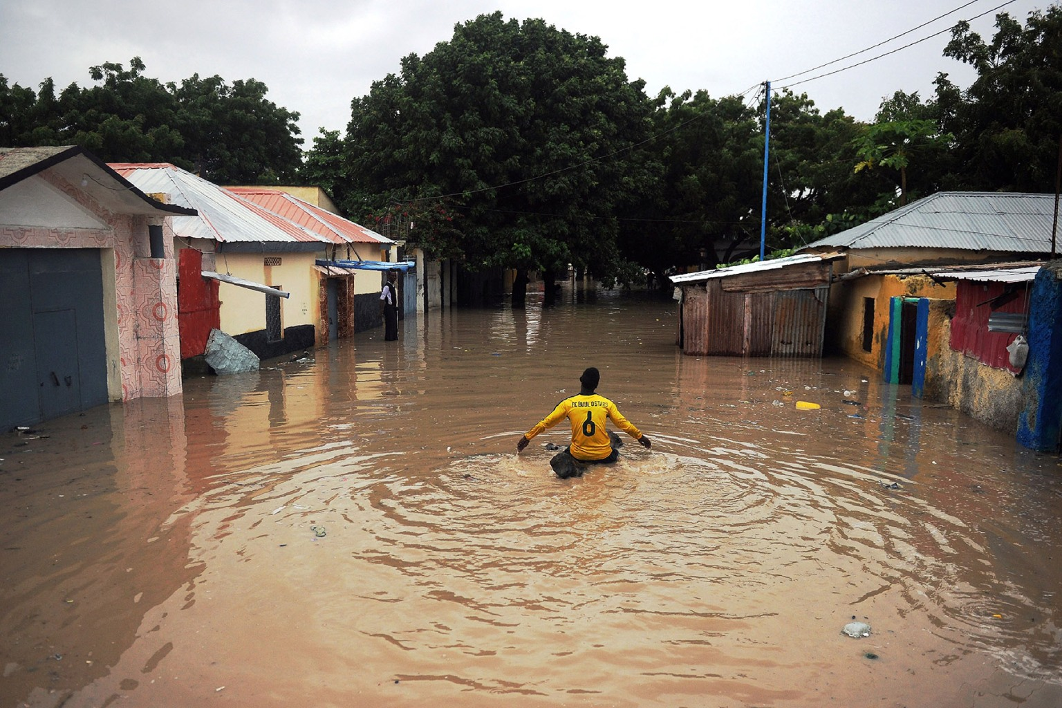 A boy on a log floats down a flooded street in the Wadajir district of Mogadishu on May 20 after homes were inundated in Somalia's capital following heavy overnight rainfall. MOHAMED ABDIWAHAB/AFP/Getty Images