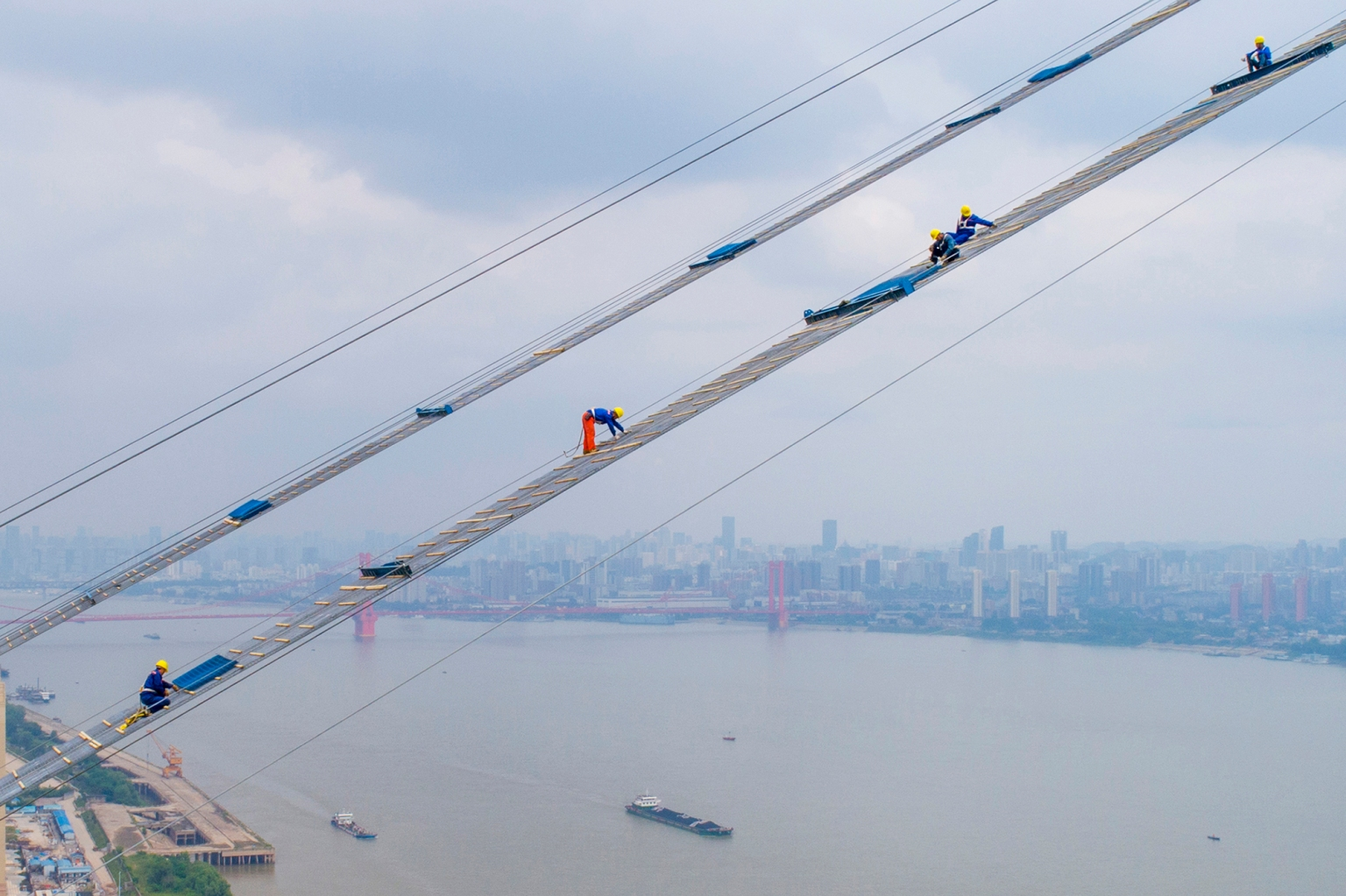 Workers labor on the construction of a double-deck suspension bridge May 8 across the Yangtze River in Wuhan, China. AFP/Getty Images