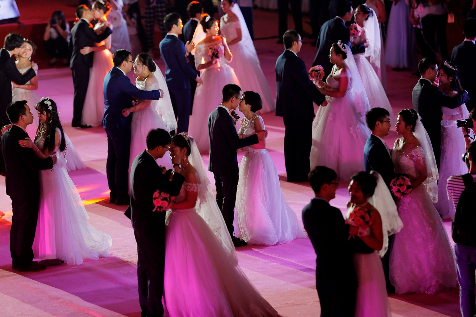 Couples kiss during a mass wedding ceremony on May 20 at Northeastern University in Shenyang in China's northeastern Liaoning province. AFP/Getty Images
