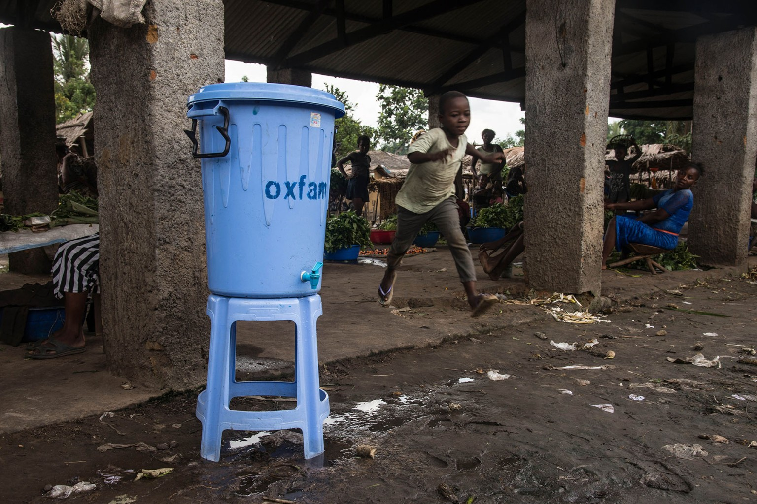 "A boy runs past a dispenser containing water mixed with disinfectant at the Congo Air Market, east of Mbandaka on May 23. An Ebola outbreak in the Democratic Republic of Congo has a clear ""potential to expand,"" the WHO warned amid news that three people infected with the deadly virus had fled a local hospital. JUNIOR D. KANNAH/AFP/Getty Images"