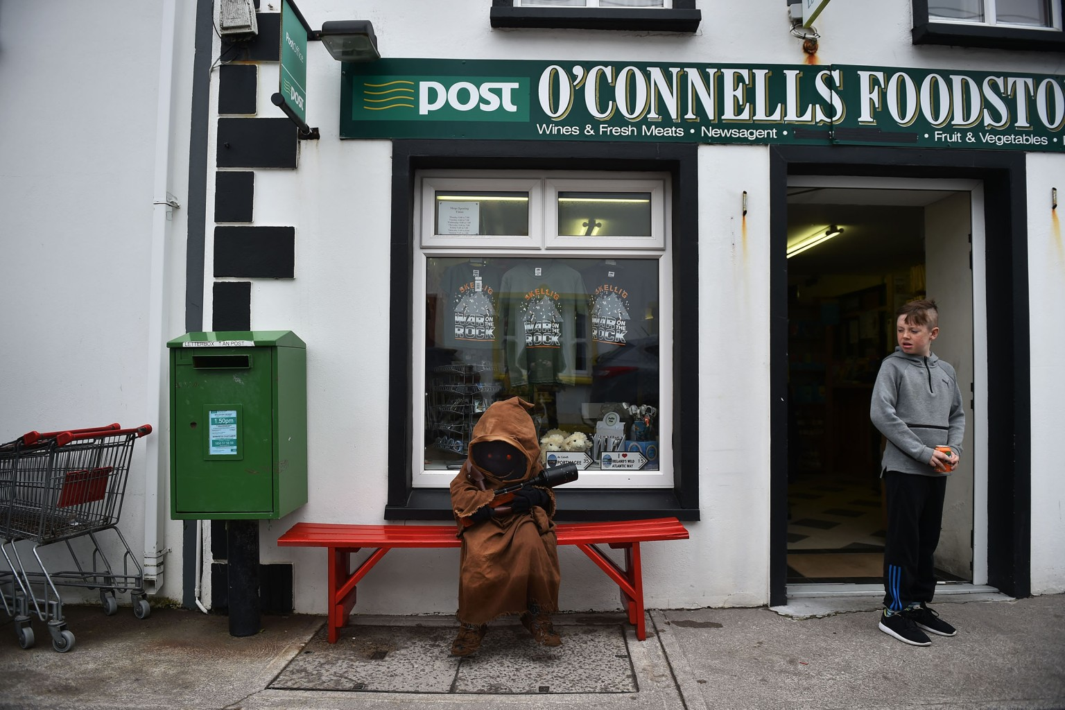 "A child dressed as a Jawa character from Star Wars sits outside a shop on May 5 in Portmagee, Ireland. The first ever ""Star Wars"" festival in the town is taking place against the backdrop of the famous Skellig Michael island, which was used extensively in recent installments of the popular science fiction saga. Charles McQuillan/Getty Images"