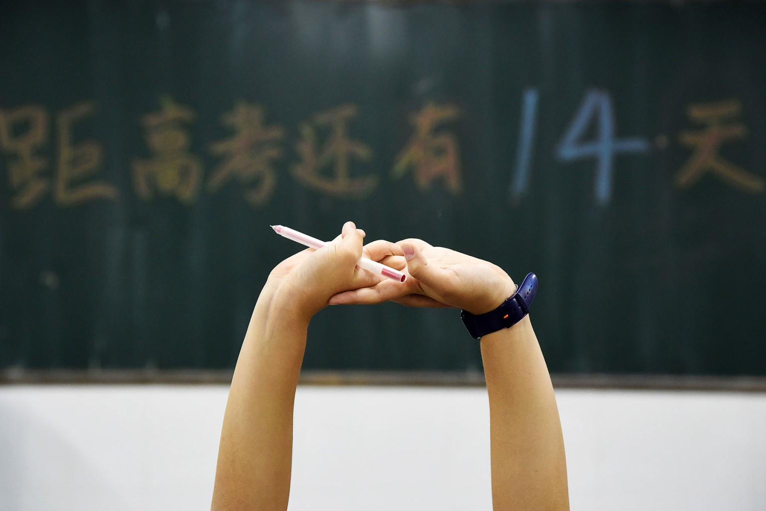 A high school student stretches May 23 as a countdown to the annual gaokao, or college entrance examinations, is written on the blackboard in Handan, China. The grueling nationwide exams take place on June 7 and June 8 this year. AFP/Getty Images