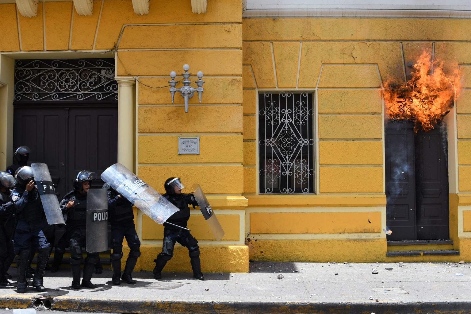 Honduran riot policemen stand outside the Municipal Government of the Central District of Tegucigalpa after demonstrators set it on fire during a May Day protest demanding the resignation of President Juan Orlando Hernandez on May 1. Thousands of workers there and worldwide took to the streets to demand better working conditions and welfare during International Labor Day. ORLANDO SIERRA/AFP/Getty Images