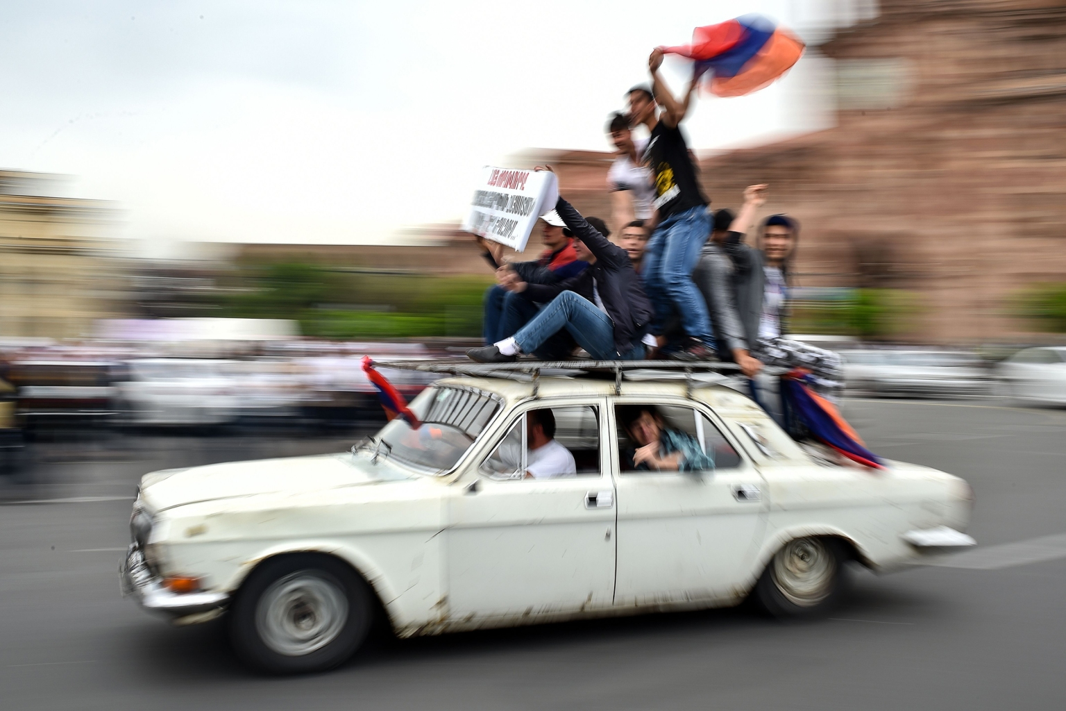 Supporters of Armenian opposition leader Nikol Pashinyan ride atop a car on May 8 in downtown Yerevan as the parliament voted to elect a new prime minister. Pashinyan, who spearheaded weeks of anti-establishment protests, won the election during the second vote in a week after he initially failed to win the ruling party's support. SERGEI GAPON/AFP/Getty Images