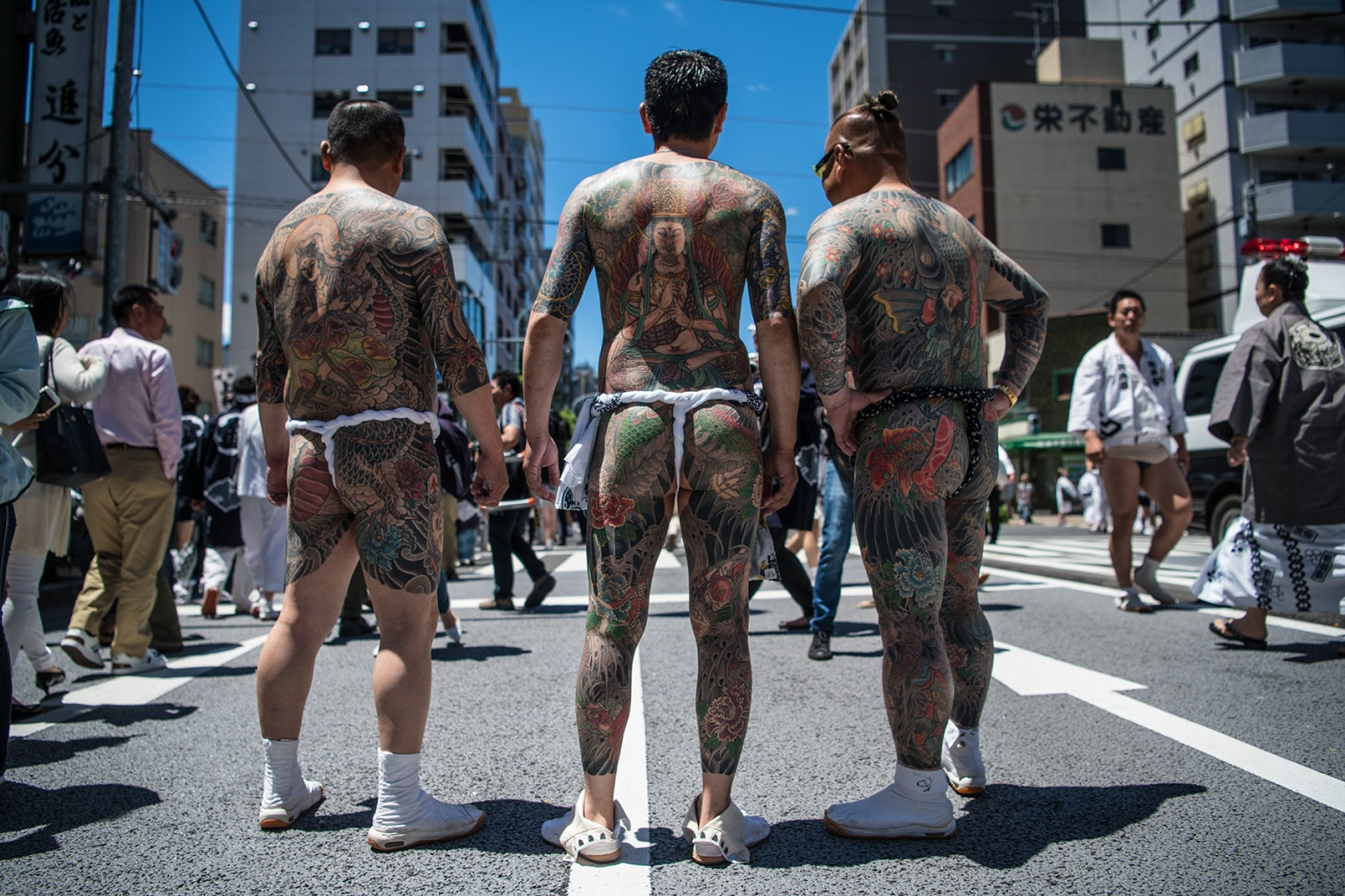 Heavily tattooed Japanese men chat in the street near Asakusa Temple on the final day of Sanja Festival on May 20 in Tokyo. The three-day festival starts with a grand parade with dancers in traditional costumes performing before portable shrines from local communities are carried to and from the temple. Carl Court/Getty Images