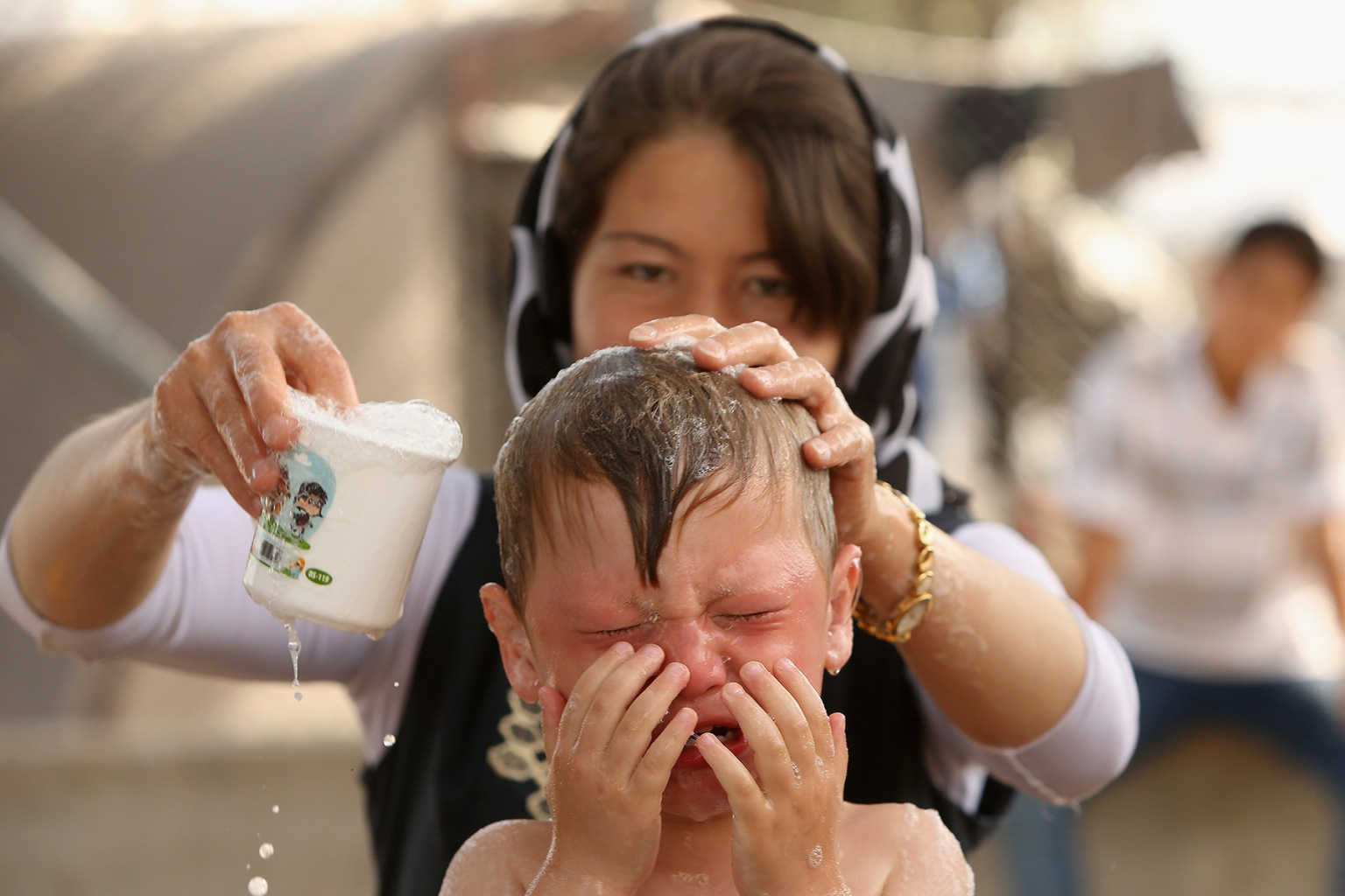 An Afghan woman gives her child a bath May 20 at the Moria refugee camp in Mytilene, Greece. The camp on the Greek island of Lesbos is home to more than 6,000 asylum seekers who crossed the Aegean Sea from Turkey's nearby shore by boat, usually at night to avoid interception. Adam Berry/Getty Images