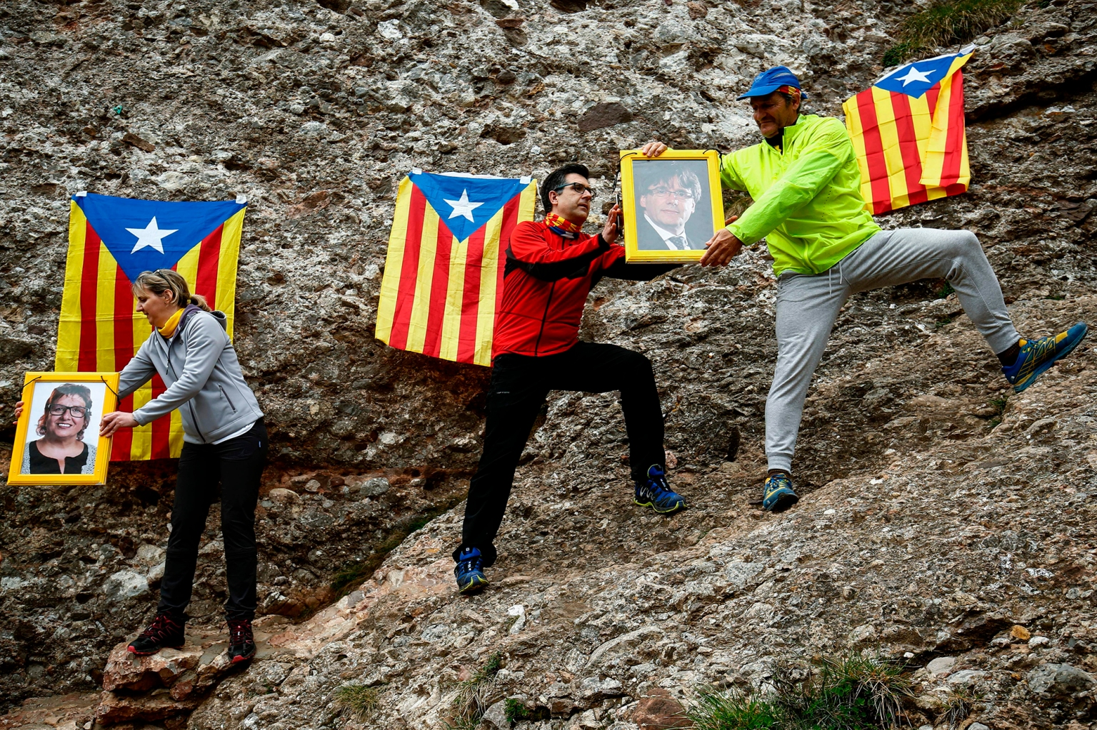 People pass along portraits of Catalonia's former president Carles Puigdemont and Dolors Bassa, former Catalan regional government counselor of labor, social affairs, and family, as they form a human chain in support of jailed and self-exiled Catalan politicians after hiking the Montserrat Mountain near Barcelona on April 28. PAU BARRENA/AFP/Getty Images