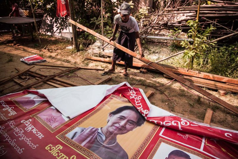 Volunteers take down posters of Aung San Suu Kyi at the National League for Democracy Party head office on November 6, 2015 in Kaw Hmu, Myanmar.