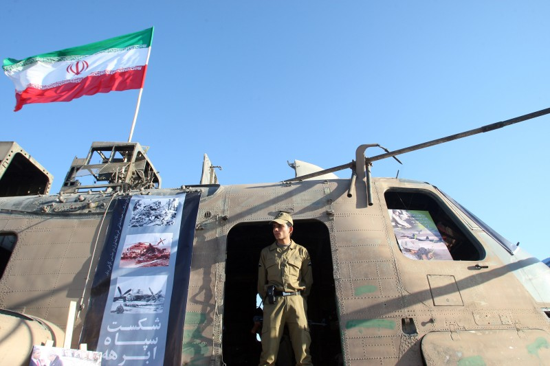 A member of Iran's Revolutionary Guard stands under a national flag on the wreckage of a captured U.S. Air Force  helicopter during a ceremony in Tehran in April 2010. (ATTA KENARE/AFP/Getty Images)