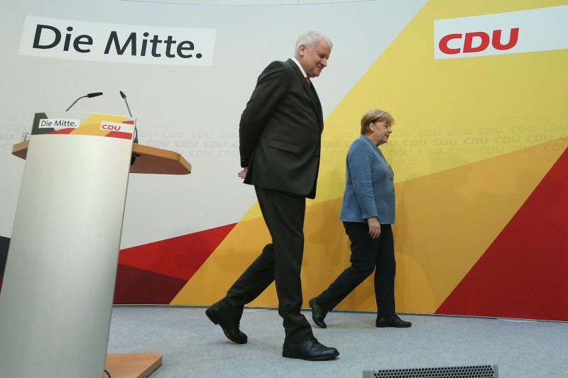 German Chancellor Angela Merkel and Bavarian Governor and leader of the Bavarian Christian Social Union (CSU) Horst Seehofer depart after speaking to the media on October 9, 2017 in Berlin.