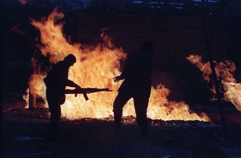 Two Chechen fighters warm by the fire burning next to a house destroyed by Russian artillery in the center of Grozny, Jan. 15, 1995. ( Michael Evsafiev/AFP/Getty Images)