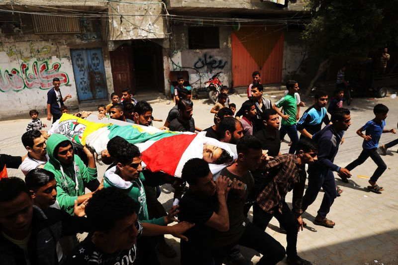 The body of Jamal Affana, 15, is brought through a Rafa alleyway in the Gaza Strip on May 13 after he succumbed to a gunshot wound. Affana was killed by an Israeli sniper while participating in demonstrations.