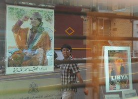 A man is reflected in a glass door as he walks past a portrait of Libyan leader Muammar al-Qaddafi displayed inside the Libyan economic cooperation office in Seoul on July 28, 2010. (PARK JI-HWAN/AFP/Getty Images)
