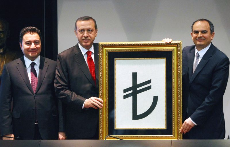 Recep Tayyip Erdogan, flanked by his deputy Ali Babacan and Central Bank Governor Erdem Basci with the symbol for the national currency, the Turkish lira, during a ceremony in Ankara, on March 1, 2012. (ADEM ALTAN/AFP/Getty Images)