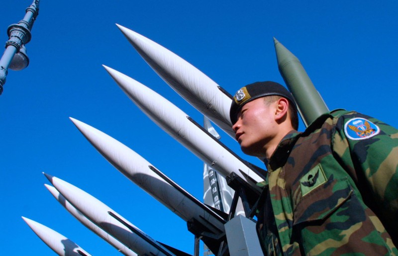 A South Korean soldier stands under a display of North and South Korean missiles in Seoul on Dec. 12, 2002. (Chung Sung-Jun/Getty Images)