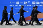 Security guards walk past a billboard for the Belt and Road Forum for International Cooperation in Beijing on May 13, 2017. (Wang  Zhao/AFP/Getty Images)