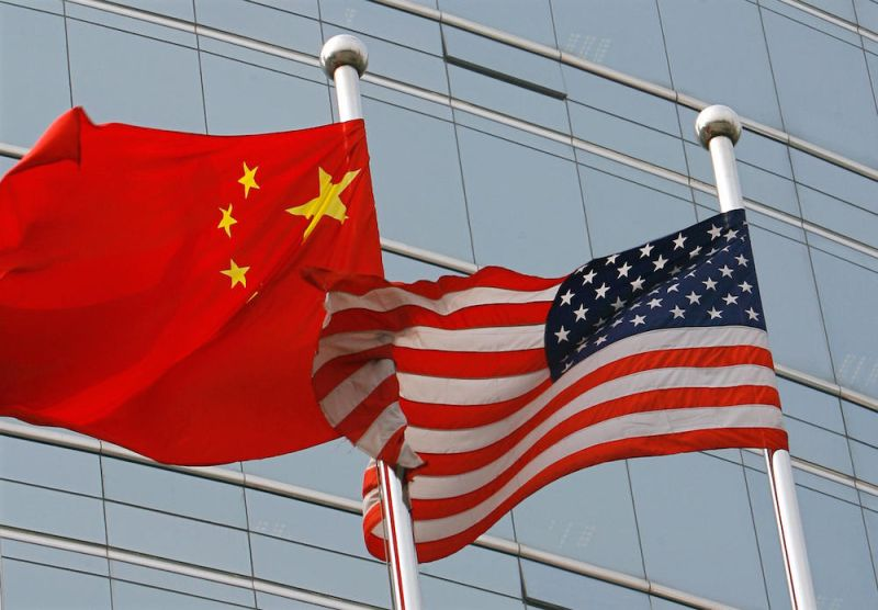 A US and a Chinese flag wave outside a commercial building in Beijing on July 9, 2007. (Teh Eng Koon/AFP/Getty Images)