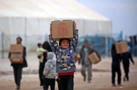 Displaced Syrians, who fled their homes in Deir Ezzor city, carry boxes of humanitarian aid supplied by United Nations Children's Fund (UNICEF) at a refugee camp in Syrias northeastern Hassakeh province on February 26, 2018. (DELIL SOULEIMAN/AFP/Getty Images)