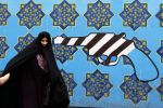 An Iranian woman walks past a mural on the wall of the former U.S. Embassy in Tehran on May 8. (Atta Kenare/AFP/Getty Images)