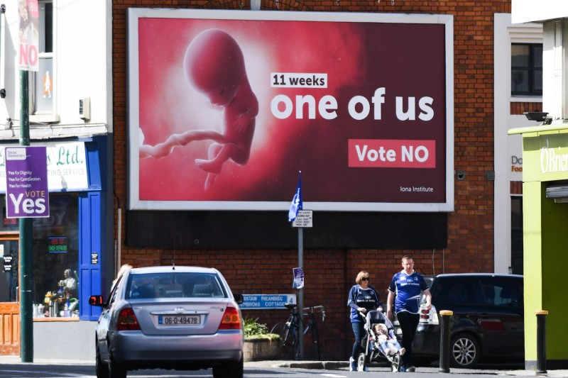 Pedestrians pass a billboard urging a 'no' vote in the referendum to preserve the eighth amendment of the Irish constitution in Dublin on May 13, 2018.