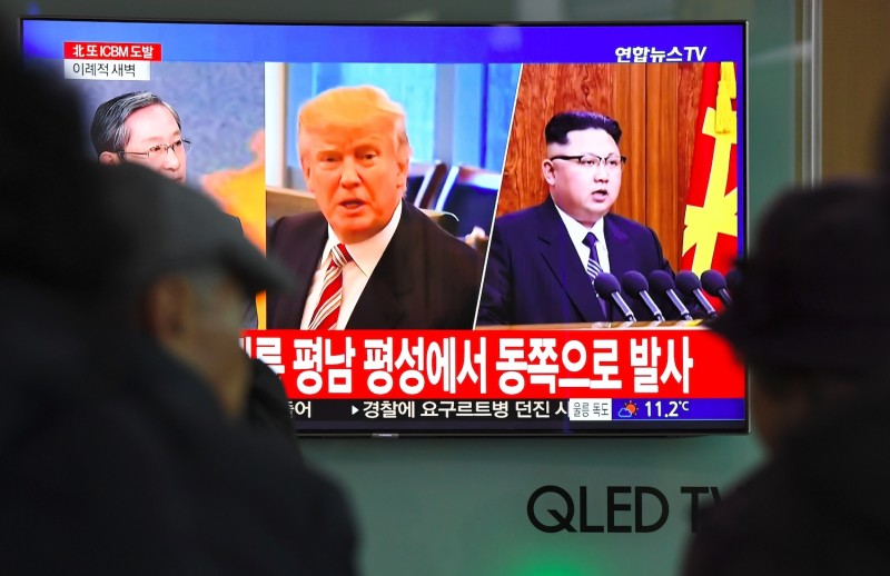 People watch a television screen showing U.S. President Donald Trump, center, and North Korean leader Kim Jong Un, right, at a railway station in Seoul on Nov. 29, 2017. (Jung Yeon-Je/AFP/Getty Images)