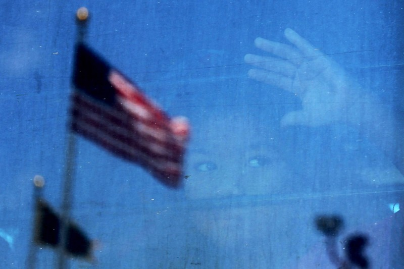A migrant child looks out the window of a bus as protesters try to block a bus carrying migrant children out of a U.S. Customs and Border Protection Detention Center on June 23 in McAllen, Texas.  (Spencer Platt/Getty Images)