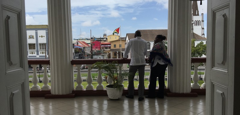 Above: Two people look over the balcony on the second floor of the Parliament building in Georgetown on April 26. Top: In a section of Georgetown called Houston, contractors are building out a new oil industry depot, capable of storing needed equipment, fuel, water, cement, fluids, and other materials that contractors working in Guyana's deep waters need. The base already has a contract to supply ExxonMobil. (Micah Maidenberg for Foreign Policy)