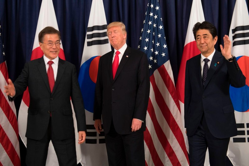 U.S. President Donald Trump (C), Japanese Prime Minister Shinzo Abe (R), and South Korean President Moon Jae-in (L) pose for photos before attending the Northeast Asia Security Dinner at the U.S. Consulate General   in Hamburg, Germany, July 6, 2017.
