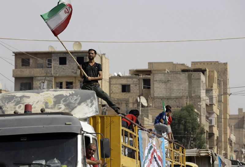 A Syrian man holds the Iranian flag as a convoy carrying aid provided by Iran arrives in the eastern city of Deir Ezzor on Sept. 20, 2017. (LOUAI BESHARA/AFP/Getty Images)