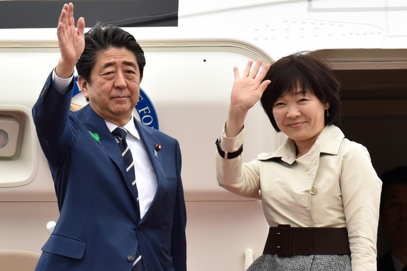 Japan's Prime Minister Shinzo Abe and his wife Akie wave as they prepare to depart from Tokyo's Haneda airport on April 17, 2018.        (Photo credit: KAZUHIRO NOGI/AFP/Getty Images)