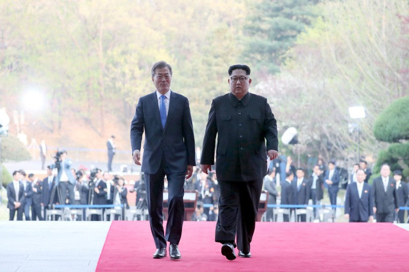North Korea's leader Kim Jong Un (R) and South Korea's President Moon Jae-in (L) walk together after announcing a joint statement near the end of their historic summit at the truce village of Panmunjom on April 27, 2018. (KOREA SUMMIT PRESS POOL/AFP/Getty Images)