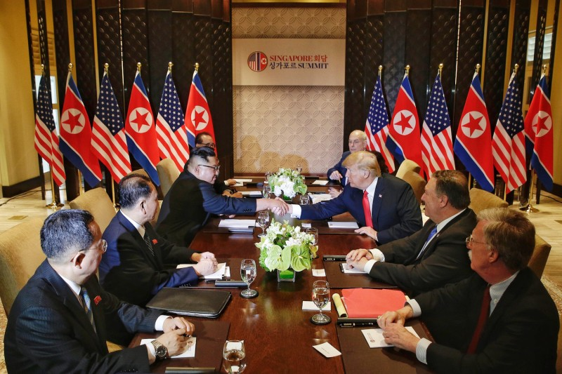 North Korean leader Kim Jong-un (L) shakes hands with U.S. President Donald Trump during their historic U.S.-DPRK summit at the Capella Hotel on Sentosa island on June 12, 2018 in Singapore.(Kevin Lim/THE STRAITS TIMES/Handout/Getty Images)