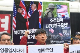 South Korean activists hold placards showing images of the Trump-Kim summit and a South Korea-U.S. joint military drill during a rally to demand a halt to the Ulchi Freedom Guardian military exercise, near the U.S. Embassy in Seoul on June 15. (Jung Yeon-Je/AFP/Getty Images)